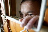 A youth looks out from the door of his detention cell inside the capital pretrial detention centre. UNICEF has improved conditions and helped implement an upgrading of services in the centre, Ulan Bat... - Jim Holmes - 23-04-2007
