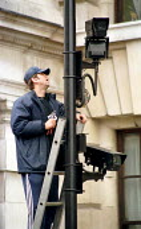 Worker fits surveillance CCTV in Whitehall London. - Jess Hurd - 06-04-2000
