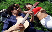 A couple relaxing smoking a spliff and playing the guitar. Legalise cannabis festival in South London. - Jess Hurd - 2000,2000s,ACE,adult,adults,asian,BAME,BAMEs,black,BME,bmes,cannabis,CIGARETTE,cigarettes,cities,city,CLJ crime law,couple,COUPLES,diversity,drug,drugs,ethnic,ethnicity,festival,FESTIVALS,getting high