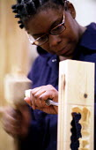 Unemployed women learn carpentry and joinery skills. Women's Education in Building (WEB) centre West London. - Jess Hurd - 2000s,2001,adult,Adult Education,adults,apprentice,Apprentices,apprenticeship,BAME,BAMEs,black,BME,bmes,building,BUILDINGS,capitalism,capitalist,Carpenter,Carpenters,cities,city,construction,course,di