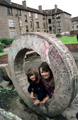 Children on playground on tenement housing on estate in Possil. Council flats boarded up but most still occupied. Glasgow housing stock due to transfered to housing company - Jess Hurd - 18-09-1999
