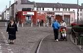 Young mother returns from the corner shop. Council housing estate, Niddrie, East Edinburgh, Scotland. - Jess Hurd - 12-04-2001