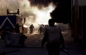Press photographer as Italian riot police run through burning streets. Genoa G8 summit. - Jess Hurd - 21-07-2001
