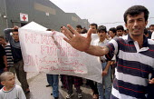 Refugees mainly Afghans, Iraqis, Kurds and Iranians with a sick child hold a protest against their treatment by the authorities, Sangatte Red Cross Refugee camp nr Calais. - Jess Hurd - 02-08-2001