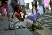 Girl takes a break to eat lunch, Notting Hill Carnival London - Jess Hurd - 2000s,2001,ace culture,BAME,BAMEs,black,BME,BME black,bmes,break,child,CHILDHOOD,CHILDREN,cities,city,diversity,ethnic,ethnicity,food,FOODS,juvenile,juveniles,kid,kids,London,meal,MEALS,minorities,min