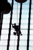 Window cleaner cleans Canary Wharf Docklands railway station roof, London. - Jess Hurd - 04-12-2001
