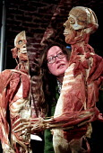 Woman looks at sliced human plastinated body at the controversial Korperwelten art exhibition, by Prof. Gunther Von Hagens MD, Brussels, Belgium. - Jess Hurd - 12-12-2001