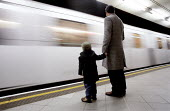 Tube train passes father and son on station platform. - Jess Hurd - 04-01-2002