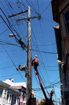 Communication workers climb telegraph poles, The Mission, San Francisco, USA. - Jess Hurd - 26-05-2002