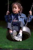 Child playing on a tyre swing, St John's Nursery School Hackney, London. - Jess Hurd - 2000s,2002,appealing,BAME,BAMEs,black,BME,bmes,CARE,carer,carers,charming,child,child care,childcare,CHILD-CARE,CHILDHOOD,childminding,children,cities,city,CRECH,creche,creches,cute,day care,daycare,d