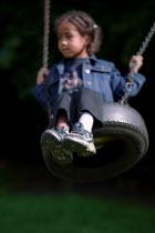 Child playing on a tyre swing, St John's Nursery School Hackney, London. - Jess Hurd - 31-08-2002