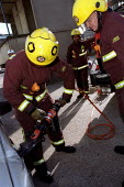 Firefighters train with cutting equipment on an abandoned car. East London. - Jess Hurd - 26-10-2002
