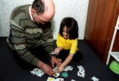 Father and daughter asylum seekers from Afghanistan play with a jigsaw word puzzle. Manchester. - Jess Hurd - 30-01-2003