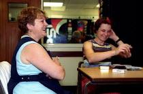 Machine operators have a cigarette break in the canteen. 3M, Sandpaper production factory, Atherstone, Warwickshire - Jess Hurd - 2000s,2002,break,break time,canteen,CANTEENS,cigarette,Cigarettes,communicating,communication,conversation,conversations,dialogue,discourse,discus,DISCUSS,discusses,DISCUSSING,discussion,FACTORIES,fac