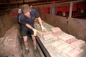 Young worker stacks bricks, Redbank Manufacturing, Producers of terracotta clayware, bricks and tiles. Measham, Staffordshire. - Jess Hurd - 09-07-2002
