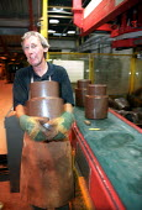 Man trims clay chimney stack, Redbank Manufacturing, terracotta producers of clayware, bricks and tiles. Measham, Staffordshire. - Jess Hurd - 2000s,2002,brick,bricks,capitalism,capitalist,ce,ceramic,CERAMICS,chimney,CHIMNEYS,clay,clayware,craft,earthenware,EBF economy,Industries,industry,job,jobs,LAB lbr Work,maker,makers,making,manual,manu