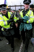 Protester arrested by police. Blockade of Faslane HM Navel Base Clyde, home of Trident nuclear submarine. Scotland. - Jess Hurd - 2000s,2003,activist,activists,Anti War,Antiwar,arrest,ARRESTED,ARRESTING,arrests,atomic,Blockade,BLOCKADING,CAMPAIGN,Campaign for nuclear disarmament,campaigner,campaigners,CAMPAIGNING,CAMPAIGNS,clj c
