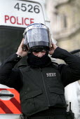 Police slip into their riot gear. May Day London. International Workers Day. - Jess Hurd - 01-05-2003