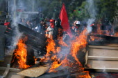 Protesters stand behind a burning barricade at anti G8 Summit protests in Geneva, Switzerland. - Jess Hurd - 01-06-2003