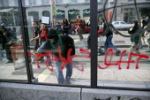 Anarchist protester spray painting a bus shelter at anti G8 Summit riot, Geneva, Switzerland - Jess Hurd - 01-06-2003