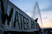 Protesters hang anti water privatisation banner from bridge in front of the Jet DEau fountain in Geneva, Switzerland. - Jess Hurd - 2000s,2003,activist,activists,Anti Capitalist,bridge,CAMPAIGN,campaigner,campaigners,CAMPAIGNING,CAMPAIGNS,capitalism,capitalist,DEMONSTRATING,demonstration,DEMONSTRATIONS,dusk,economic,eu,europe,euro