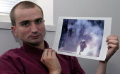 Guy Smallman photographer, with a video still showing him being attacked with a volley of concussion grenades fired by the Geneva riot police at the G8 Summit demonstrations. NUJ Press Conference, Lon... - Jess Hurd - 13-06-2003