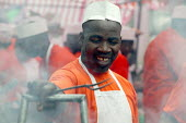 A chef cooks jerk chicken on a stall at the Notting Hill Carnival. London. - Jess Hurd - 25-08-2003