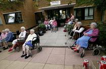 Elderly sitting outside a nursing home watching the Notting Hill Carnival. London. - Jess Hurd - 25-08-2003