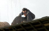 American magician David Blaine sits in a sealed perspex box suspended 40 feet in the air near Tower Bridge in London. He plans a feat of endurance, spending 44 days alone without food. - Jess Hurd - 06-09-2003