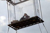 American magician David Blaine sit in a sealed perspex box suspended 40 feet in the air near Tower Bridge in London. He plans a feat of endurance, spending 44 days alone without food. - Jess Hurd - 06-09-2003