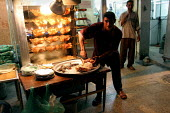 Worker prepares chicken for the restaurant customers just off Firdos Square before curfew. Baghdad, Iraq. - Jess Hurd - 07-10-2003