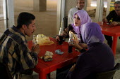 Students share a drink in the canteen at Baghdad University. Baghdad, Iraq. - Jess Hurd - , Iraqis,2000s,2003,Arab,Arabs,canteen,CANTEENS,dress,edu education,female,hajib,headscarf,higher,hijab,Iraqi,Iraqis,islam,islamic,Middle East,monotheistic,MUSLEM,muslim,MUSLIMS,people,person,persons,