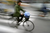 Man cycles to work on a bicycle. Shanghai, China. - Jess Hurd - 20-10-2003