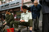 Pensioners get their knives sharpened by soldiers for free on the pavement as part of a health and wellbeing project providing services once a month on the streets of Shanghai, China. - Jess Hurd - 2000s,2003,adult,adults,age,ageing population,army,cities,city,elderly,knives,MATURE,OAP,OAPS,old,pavement,pensioner,pensioners,person,persons,project,scene,scenes,service,services,Shanghai,sharp,shar