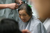 Pensioners get a free haircut on the pavement as part of a health and wellbeing project providing services once a month on the streets of Shanghai, China. - Jess Hurd - 20-10-2003