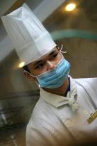 Hotel chef wearing a face mask, Zhejiang Province, China. - Jess Hurd - 26-10-2003