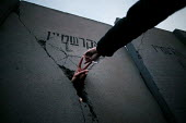 Pro Palestinian activist thrusts his hand through a replica Separation wall representing the concrete wall erected by Israeli forces through the West Bank. European Social Forum demonstration, Paris - Jess Hurd - 15-11-2003