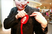 Harrods sales asssistant pins a rosette to her jacket in preparation for the opening day of the Harrods Sale. London. - Jess Hurd - 30-12-2003