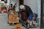 Old Chinese man repairs shoes outside his home. Old Town, Shanghai, China. - Jess Hurd - 2000s,2003,age,ageing population,Chinese,cities,city,cobbler,EARNINGS,EBF economy,elderly,EQUALITY,excluded,exclusion,HARDSHIP,impoverished,impoverishment,Income,INEQUALITY,job,jobs,Lab lbr work,livin