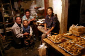 Chinese family eat their evening meal. Old Town Night Market. Shanghai, China. - Jess Hurd - 2000s,2003,baker,bakers,bakery,boy,boys,CARE,carer,carers,child,Child Care,childcare,CHILDHOOD,CHILDMINDING,children,Chinese,cities,city,DAD,DADDIES,DADDY,DADS,early years,EARNINGS,EBF Economy,EQUALIT