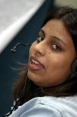 Call centre worker sells mobile phones to US clients. Infowavz Call Centre, Mumbai India. - Jess Hurd - 23-01-2004