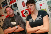 Comedian Mark Thomas and artist Tracy Sanders Wood at their exhibition of Coca Colas Nazi Adverts, London. - Jess Hurd - 2000s,2004,ACE arts culture & entertainment,art,Art Gallery,cities,city,Coca Cola,Comedy,exhibition,FACISM,FACIST,FACISTS,far right,far right,Fascism,Fascist,FASCISTS,Fine Art,funny,Humor,HUMOROUS,hum