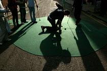 Players putt out at the Shoreditch Urban Golf Open Tournament, East London. - Jess Hurd - 2000s,2004,ACE,alternative,cities,city,Club,clubs,culture,enjoying,enjoyment,fun,funny,game,games,Golf,golfer,Hackney,hobbies,hobby,hobbyist,Humor,humorous,humour,ironic,irony,JOKE,JOKES,joking,Leisur