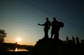 Sun sets on the Green Bridge with its Socialist Realist statues of workers, remnants of Soviet occupation as Lithuania prepares to join the European Union. Vilnius, Lithuania. - Jess Hurd - 30-04-2004