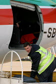 Lithuanian Airlines baggage handlers load an aircraft for take off. One of the first flights to leave the country on 1st May as Lithuania joins the European Union. Vilnius, Lithuania. - Jess Hurd - 01-05-2004