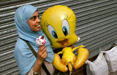 Muslim woman enjoys a fairground at the opening of The London Muslim Centre, East London. - Jess Hurd - 2000s,2004,a,ACE culture,adolescence,adolescent,adolescents,asian,BAME,BAMEs,black,BME,bmes,cities,city,communities,community,disney,diversity,dress,eating,ethnic,ethnicity,fairground,female,females,f
