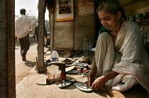 Woman fixes flip flops in her shanty town shoe repair shop. Jogeswari, Mumbai, India. - Jess Hurd - 23-01-2004