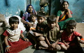 Family pose for a photograph in their shanty town home, Mumbai, India. - Jess Hurd - 23-01-2004