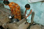 Child watches as her mother collects water from a pump. Jogeswari, Mumbai, India. - Jess Hurd - 23-01-2004
