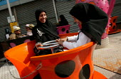 Young girls on a fairground ride at the Opening The London Muslim Centre, East London. - Jess Hurd - 12-06-2004